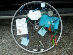 """Bicycle wheel upcycle. Collage.  Found this idea on a blog called """"The Ginger Penny Pincher."""" This is my creation based on their cool idea! It's a bike wheel/bulletin board for my best friends baby shower. :-) Includes baby shower invitations, notes, and an """"It's a boy"""" sign from the reveal party. The original idea used painted clothespins and black and white pictures! It was really cool!"""