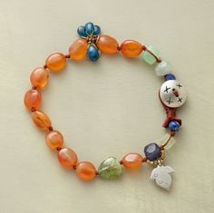 "CARNELIAN NUGGET BRACELET -- Smooth carnelians dominate half the strand, the other half peppered with lapis, aquamarine, chrysoprase, apatite, peridot and iolite. Handmade with sterling silver leaf charm and button clasp. Exclusive. Approx. 7-1/2""L."