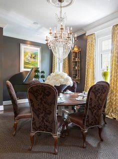 Dining room Joy Tribout Interior Design.  Loving the brown and yellow color combo, round table, fabulous chair and the chandelier!