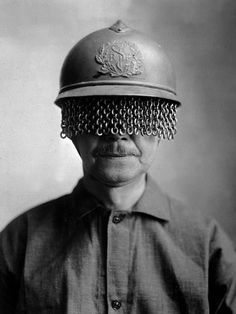 1918 A man models a steel helmet covered with a built-on chain screen to protect a soldier's eyes from rocks, shells and other fragments during World War I. It was created by E J Codd Company of Baltimore, Maryland. (War Department photo.)