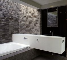 Beautiful textured stone wall in a bathroom designed by the Belgian interior architects iXtra/Filip Vanryckegem.