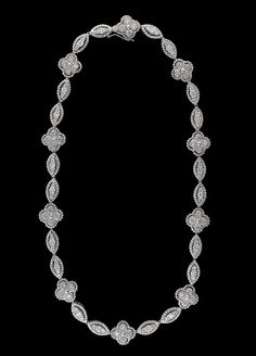 A diamond and eighteen karat white gold necklace. navette and quatrefoil links set with round brilliant-cut diamonds; total diamond weight approximately: 6.40 carats. Gross weight: 37.4 dwt.; Length: 15.5 in.