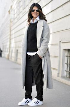 Winter Street Style: Layered black sweater over a white button up. Worn with long wool gray coat, black trousers and Adidas sneakers.