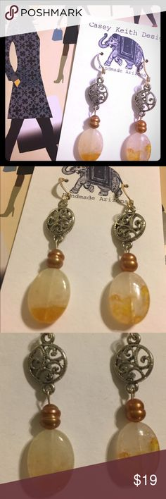 Citrine Swirl Earrings Natural citrine dangles below bound freshwater pearls & a lightweight metallic swirl on silver plated earwires. A charming method of deflecting negative vibes using stones and the watery powers retained by the pearl - for you to wield as desired to remove obstacles. Casey Keith Design Jewelry Earrings