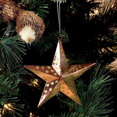 """Nothing says the holidays like a shining star. The perfect piece to adorn your tree, window, mantelpiece or anywhere else in your home, the 5"""" star is made of pounded metal with brass paint coating and comes with an elegant string for hanging. Imported."""