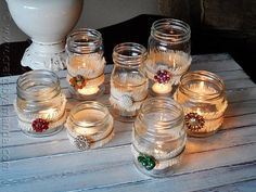 Dress up a mason jar with vintage clip on earrings and brooches. The ones in this photo have little bands of burlap, which adds a nice contrast to the shiny jewels.  Photo:  Crafts By Amanda