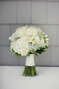 White roses, petite roses, hydrangea, babys breath I like that its a different spin on the traditional white bouquet.