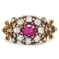 An exquisite Georgian-era rarity, this yellow gold ring features a pink sapphire in a delicately ornate design, accented by majestic old mine cut diamonds (approx. 0.58 total carat weight).