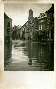 Zwolle- de Blijmarkt bij hoog water op 14 januari 1916. Op nr. 21 stalhouderij H. Bosch (nu creatief centrum De Muzerie). Op de achtergrond de Peperbus. Voor het gereedkomen van de Afsluitdijk in 1933 stond de Zuiderzee nog in open verbinding met de Noordzee. Dat maakte Noordwest-Overijssel nogal kwetsbaar. Wanneer het onstuimig weer was kon het ook in de omgeving van Zwolle flink spoken. Het opgestuwde water drong door tot in de IJssel en het Zwarte Water. Bij hevige storm en…