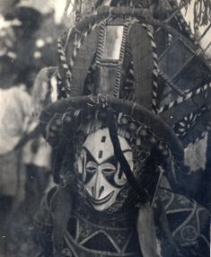 North Nigeria, head and shoulders portrait of Ibo adult male wearing masquerade costume. Close-up of mask, elaborate head-dress and patterned shirt. Medium: Gelatin silver print.