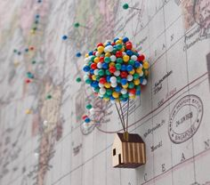 This pin holder is made to look like the floating house from the Pixar movie UP, as it's a tiny house attached to a bunch of pins that look like balloons. How it works is, a ball made of cork is on th...