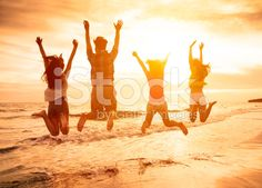 group of happy young people jumping on the beach royalty-free stock photo