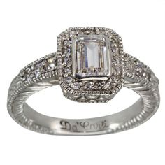 Vintage Emerald Cut Halo Diamond Engagement Ring Setting With Milgrain -  This is a Vintage Emerald Cut Halo Diamond Engagement Ring Setting With Milgrain. This ring can accommodate between a 0.50ct and 0.75ct emerald cut center diamond. This bezel set engagement ring is adorned with 0.33cts of brilliant round diamonds. These diamonds cover the shoulders of the shank and enhance the center diamond.    The shank is edged with milgrain details. Our emerald cut halo ring settings have thick…