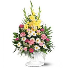 One arrangement with pink carnations and asters, white daisies, yellow gladioli and soft foliages is delivered in a white funeral basket with handle.