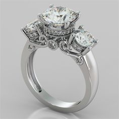This extraordinary round cut three-stone engagement ring is truly a work of art. A stunning round center stone set high on a signature regal crown is flanked by 2 equally stunning round stones and decorated with beaded pave stones. A luminous peek-a-boo stone set amidst the gallery is surrounded by artistic see-through filigree scrolls completing a dazzling look she will absolutely love.<br /> <br /> Exquisitely made to order according to your selection of precious metal, this <br…