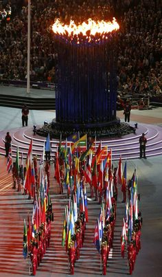 Athletes with mnational flags stand near Olympic Torch during closing ceremony of London 2012 Olympic Games at Olympic Stadium