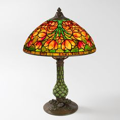 "A Tiffany Studios New York ""Crocus/Tulip"" leaded glass and patinated bronze table lamp. A bouquet of deep amber, red, gold and yellow hued crocus blossoms with hints of red in various stages of bloom decorates this shade with a sunset ground. The shade sits atop a four footed ""Pineapple"" base - See more at…"