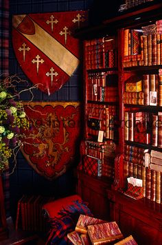 A library entirely decorated in a Scottish theme with a display of heraldic shields is furnished with a set of bookshelves displaying tartan-covered boxes and leather-bound books