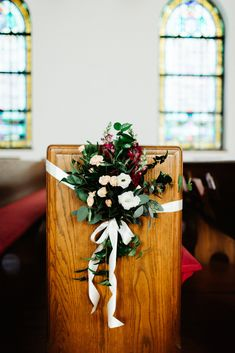 pew marker of burgundy snapdragon, peach mini carnations, white lisianthus, seeded eucalyptus, and magnolia is fastened with ivory satin ribbon.