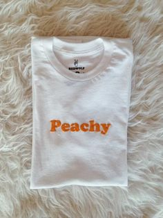 Peachy Tee Sizes S, M, L, XL, XXL Available in white with peachy lettering. 50% Polyester, 50% Cotton Made and printed in small batches in the USA