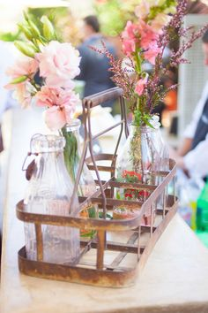 Pink flowers were placed in vintage milk bottles for a sweet centerpieces. |  Photo by Shaun & Skyla Walton, Flowers by Greenwich Floral Design