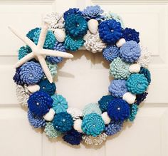 Beach Cottage Pinecone Zinnias Wreath. Each wreath will be painted in Oceanic colors and will is reminiscent of a real zinnia flowers. Each Pinecone is descaled and hand cut, painted and then wired upside down to look like a Zinnia. Inside each Pinecone Zinnia is a faux pearl and also added is a starfish and some sea shells. A 12 wire wreath form is used and when finished the wreath is about 15 in diameter and will contain approximately 40 or more pinecones ranging from small to large…