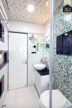 Third washroom, The Daughter's Washroom by home makers interior.  Curvy designs to give it a feminine feel...  Crafty and lovely butterfly shape carved mirrors White round basin Butterfly design false ceiling Shades of grey bisazza with open storage behind the WC.