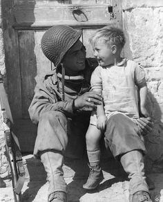 US Army Private First Class Fred Linden of Detroit, Michigan, 38th Infantry Regiment, 2nd Infantry Division, holds a young French boy following the liberation of the village of Trévières during the Battle of Normandy, 10 June 1944. Photographer: Roger Hamilton, Army Signal Corp.