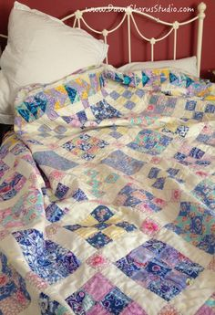 'Summer Blues' nine patch hand quilted quilt lying on an unmade bed. © Stephanie Boon, 2016 www.DawnChorusStudio.com