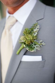 Winter-ish green boutonnière on gray suit (I so want to get married so my friends get to use some like this one).