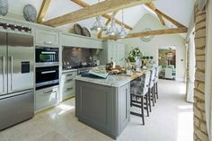 This beautiful handmade country style kitchen with Shaker style cabinets and large central island by Rixon Architects of Cirencester also features our Cotswold style Castile limestone flooring. #FlagstoneFlooring #LimestoneFlagstones #CotswoldFlagstones