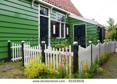 white wooden picket fence in front of a typical dutch h