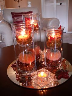 """Faux leaves and votive candles were placed on gold glass beads in the inserts on top. Glittered pumpkins are placed on orange """"ice"""" chunks inside the bottom of the cylinder vases"""