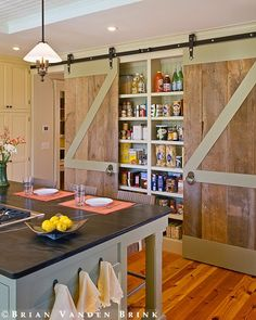 barn doors covering the pantry - such a great look!  Hardware can be purchased at the Local Feed store where farm and ranch implements are sold.  100 times easier than putting a door in a frame!