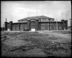 "Exterior view of Pavilion (also called National Amphitheater or ""Old Stadium"") on 46th Avenue built by Denver Union Stock Yard Company at cost of over $ 200,000, Denver, Colorado; construction began in May, 1908 and was completed by January, 1909 in time for National Western Stock Show; dog, horse-drawn carriage & horseback rider in front of pavilion or stadium. Taken in 1909 or 1910."