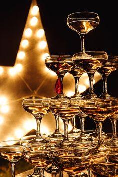 Пирамида из бокалов с шампанским, звезда в стиле старый Голливуд и свечи  -  атрибуты свадебной вечеринки.