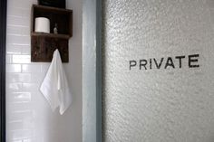 "Subway tile, vintage door with ""private"" sign."