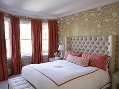 Love this golden, foily flower wallpaper with the salmon curtains.  The plush headboard adds a nice effect as well.