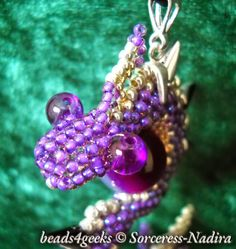 Beads4Geeks: Violet Beaded Dragon Pendant. Made with Toho Round seed beads, wrapped on a violet agate. Available on Etsy: https://www.etsy.com/listing/200737129/beaded-violet-dragon-pendant?