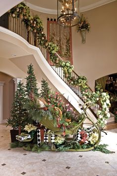 Foyer and stairway decked out for Christmas. Sleigh.