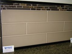 Elongated subway tiles with band of textured stone strips