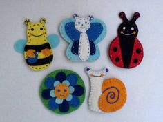 Five hand-sewn, ca. 3 inch (7,5 cm) high felt puppets: ladybird, bee, butterfly, meadow snail and a smiling blue flower.