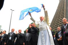 Pope Francis waves an Argentine flag during World Youth Day 2013. Credit: Alex Mazzullo/JMJ Rio 2013 via Flickr (CC BY-NC-SA 2.0).