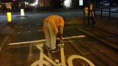 While putting down road markings, this maintenance worker demonstrated how to create a bicycle road sign.He carefully followed the outline of the bike and poured the white paint into what looks like a