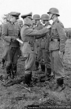 Waffen SS foreign volunteers are decorated with the Iron Cross, 2nd class, somewhere on the Eastern Front, 1943. The Waffen SS, unlike the regular army, did not hesitate to award honors to their fighting men with the simple recommendation from a commanding officer and, usually, the corroboration of two witnesses.
