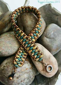 Playing around with different colors this design came together quite nicely. Moon dust turquoise and opaque white picasso superduo seed beads embellished with 8/0 and 15/0 bronze toho seed beads held together with an antique copper hitch clasp.: