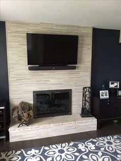 Our old fireplace was 80's/90's brick veneer. To give it an update without spending major $$$, we just went right over the top of the brick as it saves in time and labor $. With some research online and locally you get get tile at some great prices and get a fresh updated look!