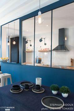 Une grande verrière bleue sépare la cuisine de cette salle à manger.