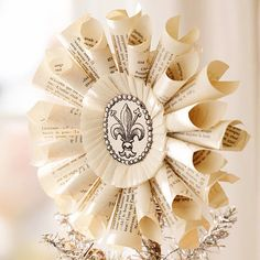 Fleur-De-Lis Medallion Tree Topper. Rolls of old book pages come together in this pretty paper tree topper with a vintage feel.