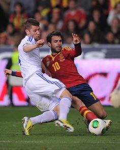 Cesc Fabregas of Spain is tackled by Joona Toivio of Finland during the FIFA 2014 World Cup Qualifier Spain v Finland.